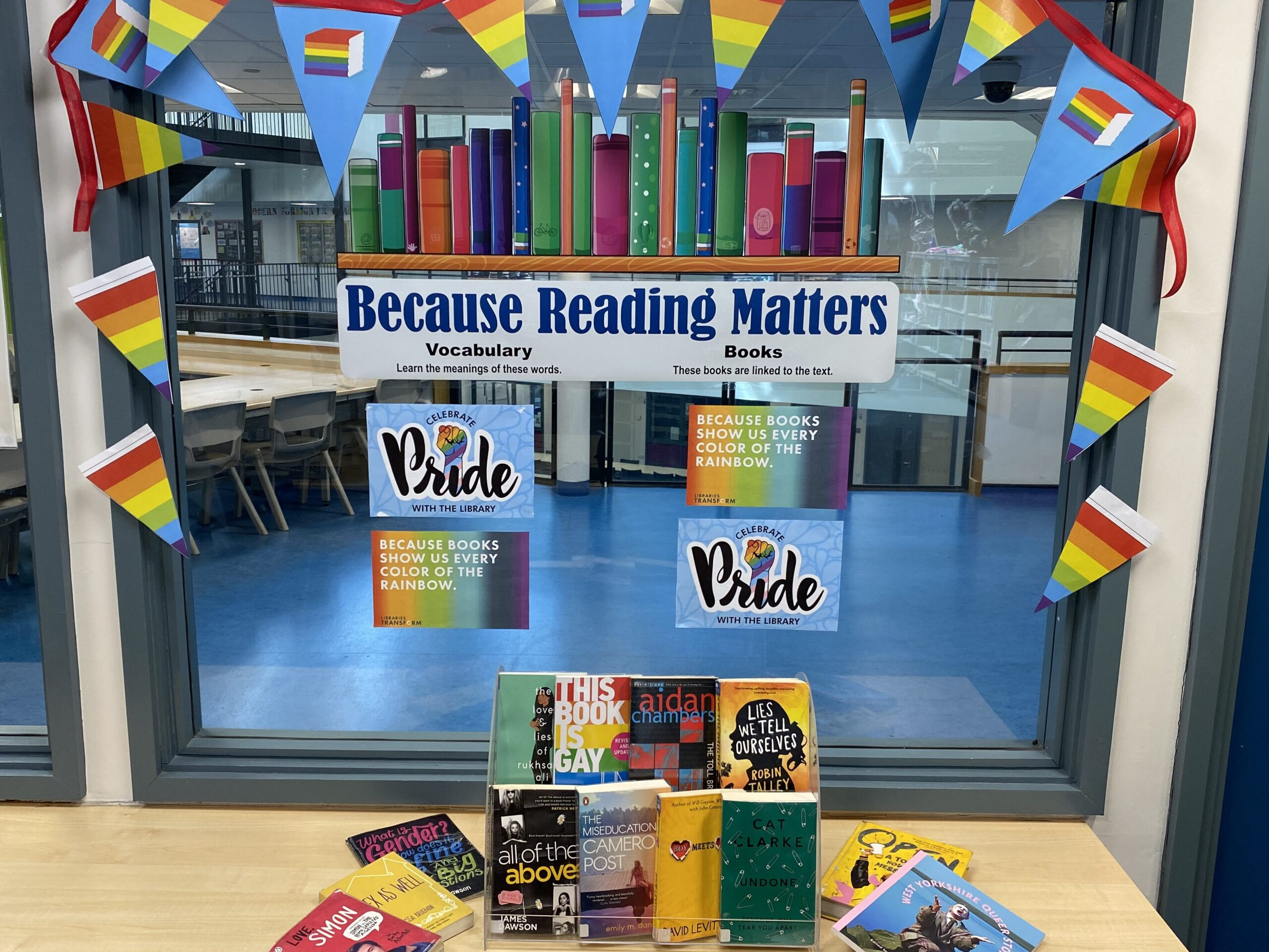 A display of books, pride posters and pride flags.