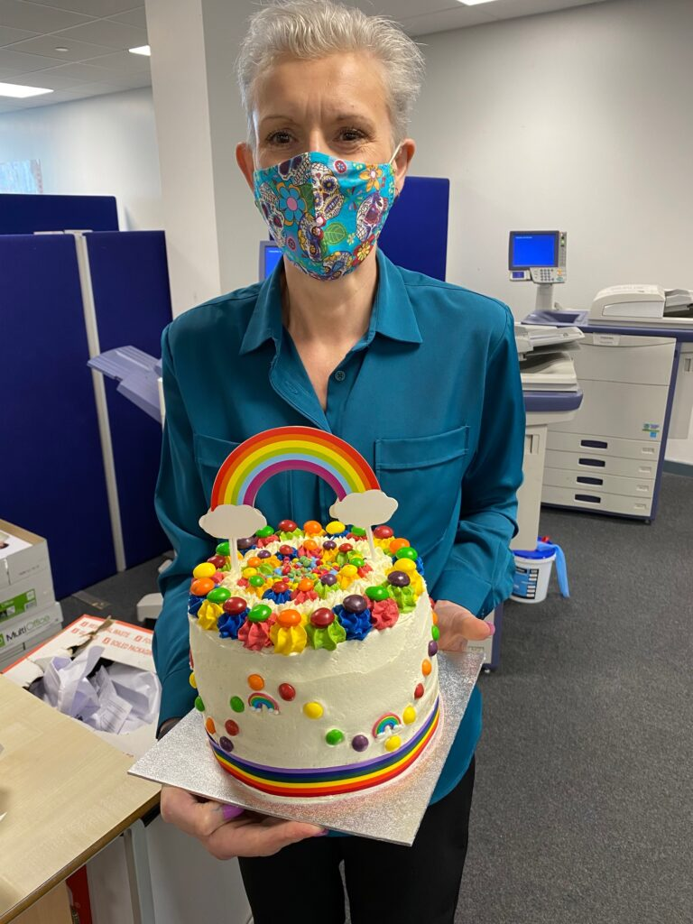 person holding a cake. Cake has a rainbow and multiple colours