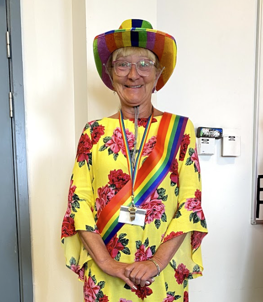 Person wearing bright colours, rainbow sash and rainbow lanyard